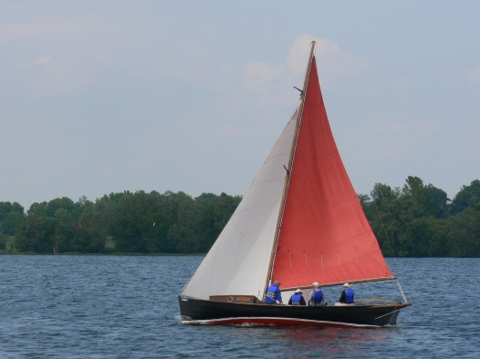 "After thousands of volunteer hours by the Marine Museums restoration boat building crew, the ""Mowat"" boat sets sail in Kingston Harbour. She is named after her last owner, the late Angus Mowat (father of Farley) who rescued the boat and then re-rigged her as a sloop. The restoration was preceded by extensive research. Her symmetrical lines are just visible."